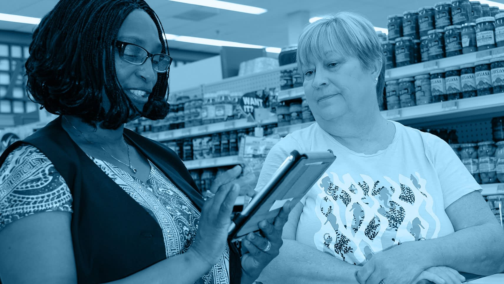 Two women conducting customer research in a supermarket